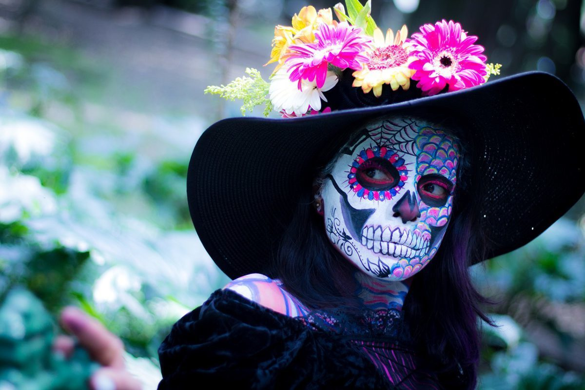 day of the dead painted face under flower hat