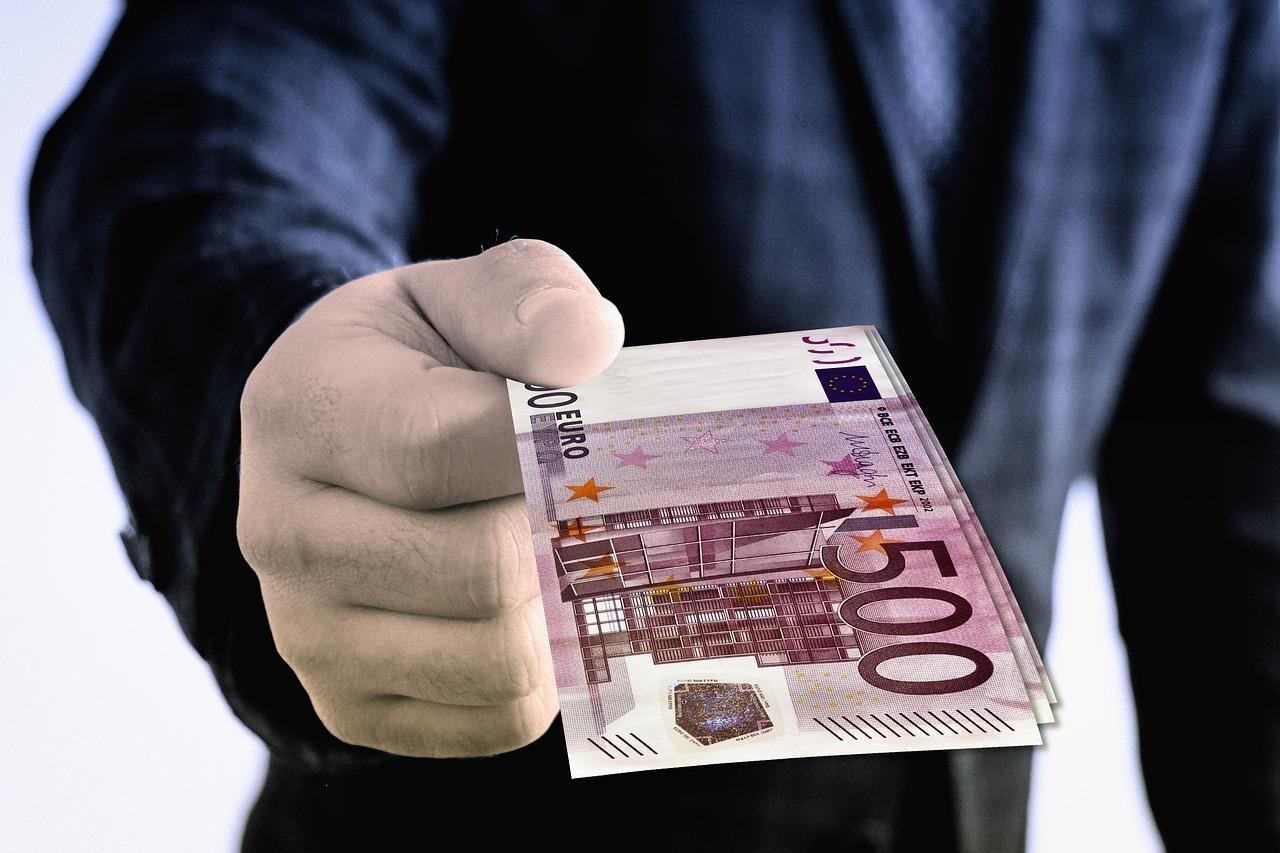 hand giving 500 euros
