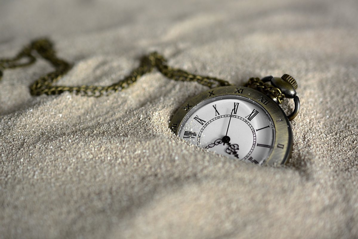 pocket watch buried in the sand