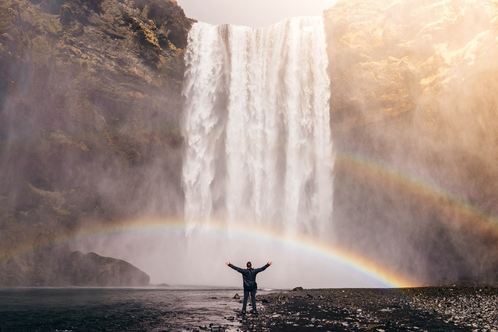 Person standing in front of waterfall on edge of river rainbow in background