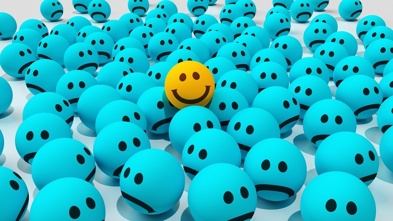 yellow smiley face in sea of blue gloomy faces