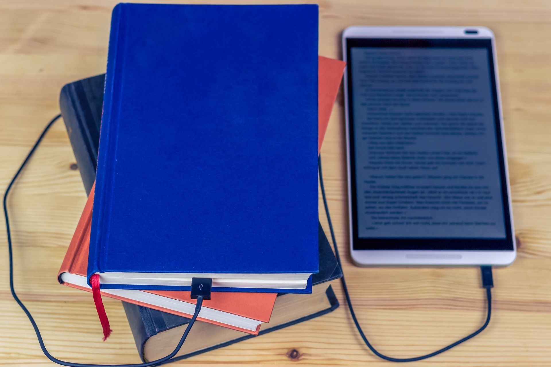 ereader plugged into a hardcover book