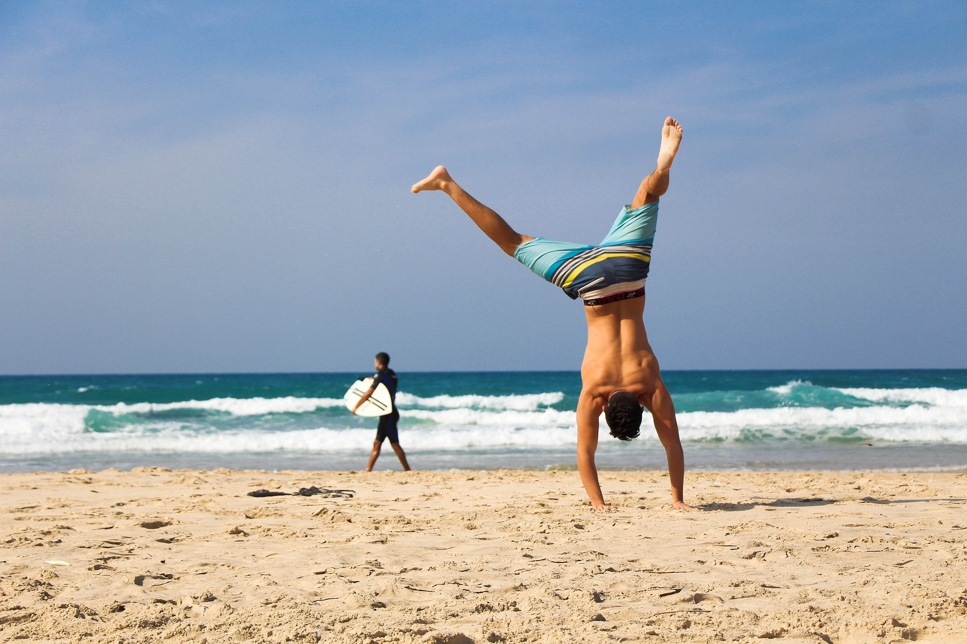 guy doing handstand on the beach