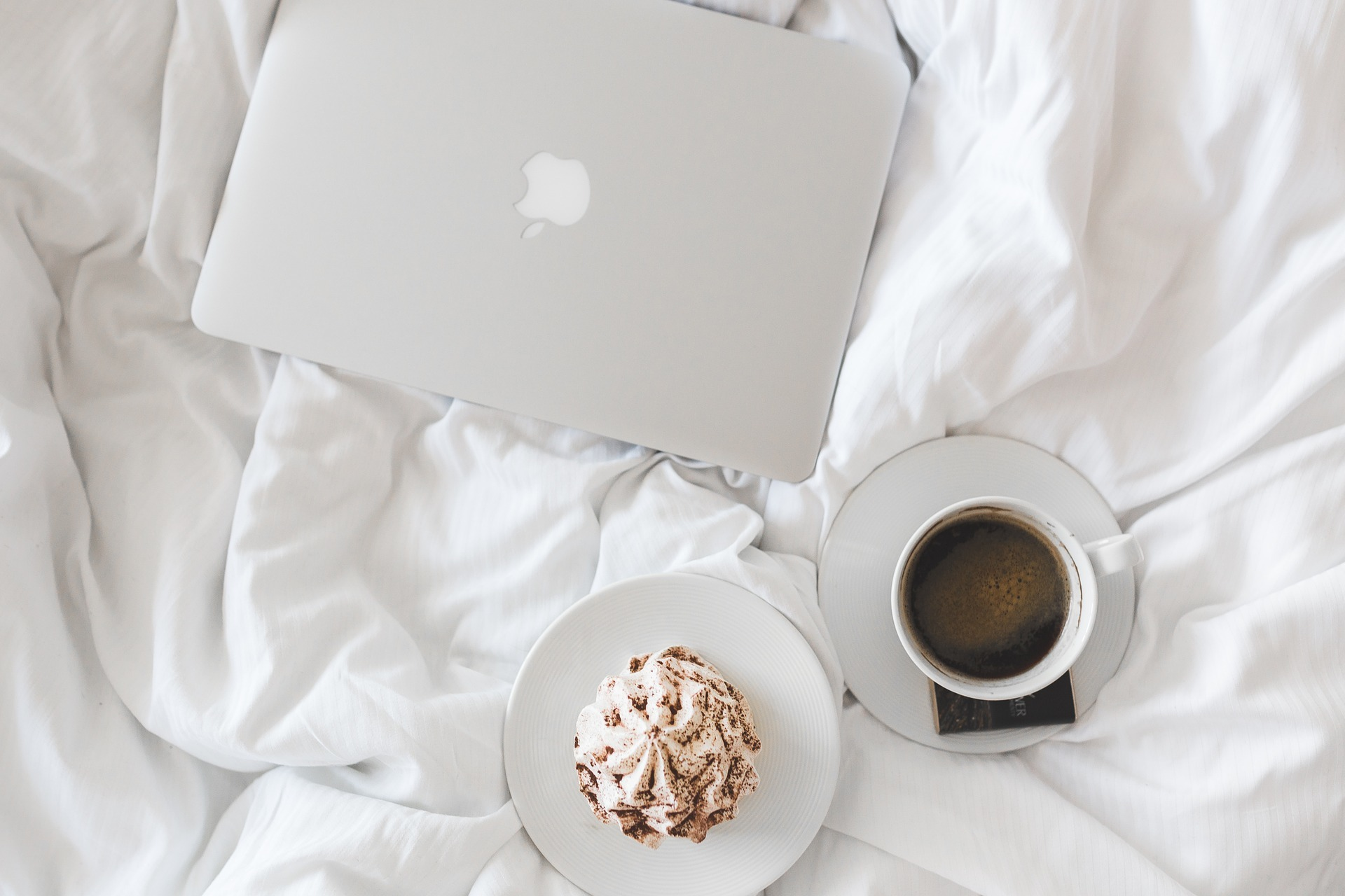 Laptop on bed with coffee and sweets